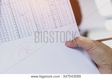 Education Evaluation Concept : Teacher Holding Grade Tests Paper And Write Ok Word In Table Score Re