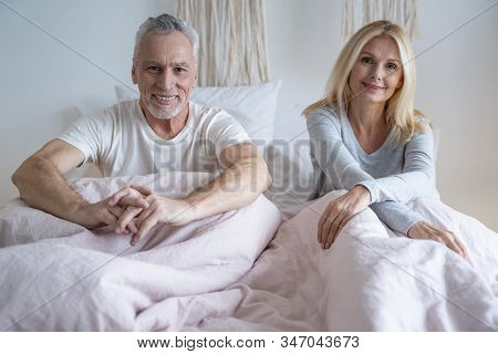 Mirthful Mature Couple In Their Bedroom Stock Photo