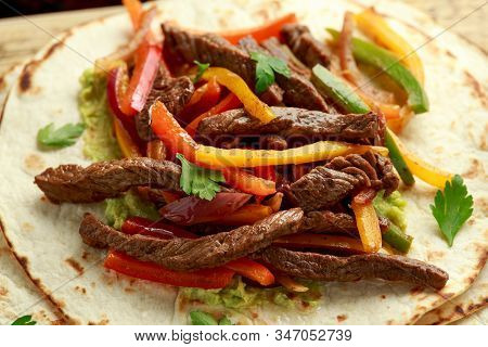 Beef Steak Fajitas With Tortilla Mix Pepper, Onion And Avocado On Wooden Board