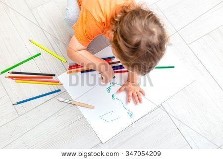Curly Girl Draws With Pencils On A White Sheet Of Paper At Home. Flat Lay