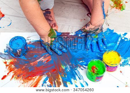 Children's Hands And Feet In Blue Paint. Finger Paints. Baby Artwork.