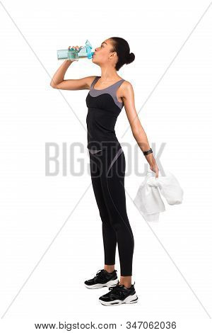 Fitness Lifestyle. Slim Black Lady In Fitwear Drinking Water Standing Over White Studio Background.