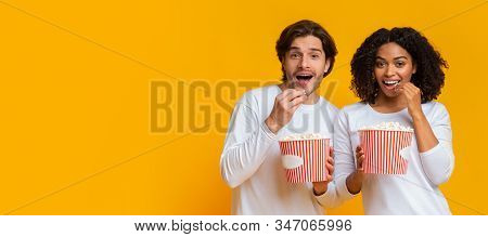 Exciting Movie Concept. Young Interracial Couple Eating Popcorn From Buckets And Looking At Camera,
