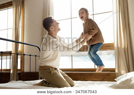 Overjoyed Little Girl Play With Loving Dad Jumping In Bedroom