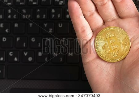 Woman Hand Holding Golden Coloured Bitcoin Coin In Her Hand Over Blurred Black Laptop Keyboard Space