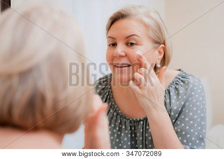 Happy Healthy Mature Woman At Mirror Apply Anti Aging Moisturizing Cosmetic Cream On Face, Smiling M