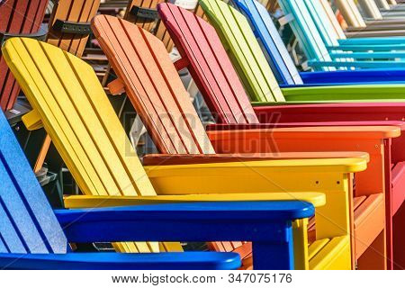 A Row Of Bright And Colorful Adirondack Chairs