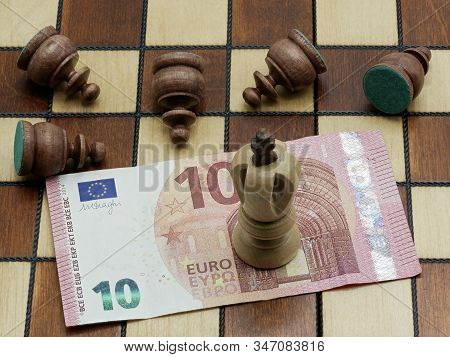 Money Rules Concept: King Chess Piece Standing On A 10 Euro Banknote With Defeated Lying Pawns On A