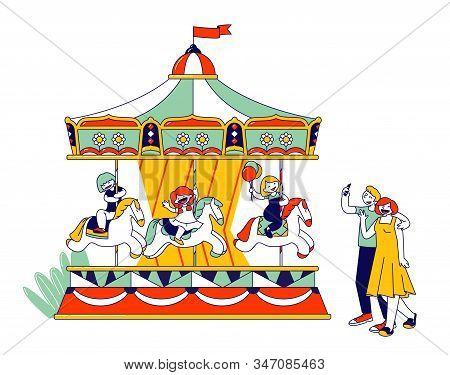 Children Riding Merry-go-round Entertainment Carousel In Recreation Park. Parents Making Photo Pictu