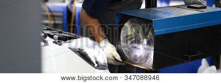 Close-up On Male Mechanic Hands Holding Big Replaced Headlamp And Making Headlight Ready Plunge In S