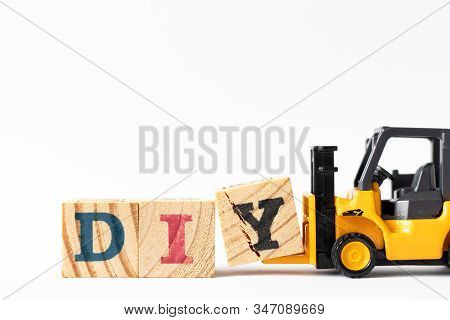Toy Forklift Hold Wood Letter Block Y To Complete Word Diy (abbreviation Of Do It Yourself) On White