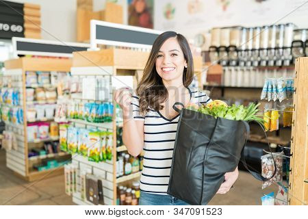 Smiling Beautiful Woman Showing Reward Card While Carrying Vegetable Bag In Supermarket