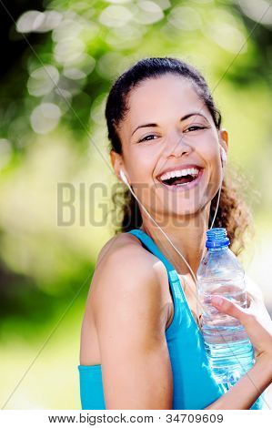 Portrait of a runner listening to music on headphones and holding water bottle. healthy wellness fitness lifestyle.