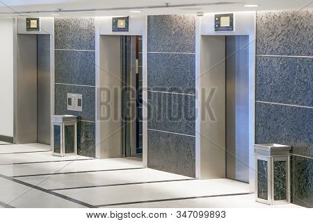 Three Elevator Doors In Office Building. Wide Angle View Of Modern Elevators With Doors. Elevators I