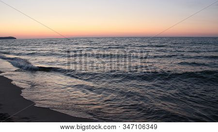 Sunset On Baltic Sea. Baltic Sea Coast During Scarlet Sunset. Waves On Seashore In Evening