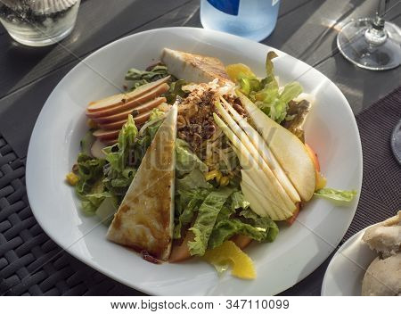 Close Up View Of White Plate With Fresh Vegetable Salad With Homemade Goat Cheese, Lettuce, Pear And