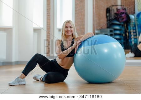Healthy Tired Sporty Woman Sitting Near Fitball And Resting