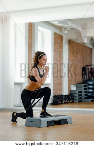 Portrait Of Strong Fit Woman Training With Stepper In Modern Fitness Club