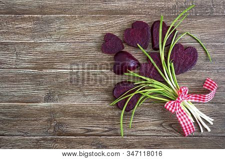 A Bouquet Of Flowers From Slices Of Boiled Beets And Green Onions On A Wooden Background. To Love Be