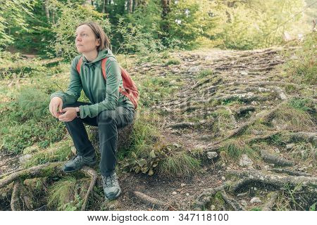Female Hiker Resting And Contemplating In Forest, Taking A Break From Trekking Outdoor Activity In W