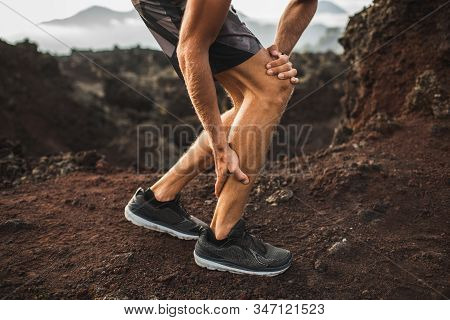 Male Runner Holding Injured Calf Muscle And Suffering With Pain. Sprain Ligament While Running Outdo