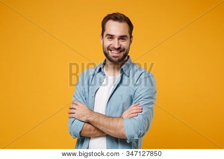 Smiling Young Bearded Man In Casual Blue Shirt Posing Isolated On Yellow Orange Wall Background, Stu
