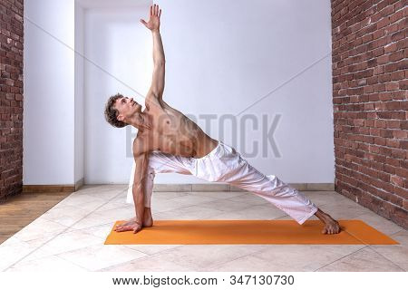 Sporty Man Practicing Hatha Yoga In Studio. Male With Naked Torso In White Pants Staying In Parivrtt