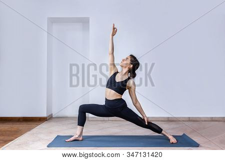 Side View Portrait Of Brunette Young Woman Wearing Sport Clothes Working Out Against White Wall, Doi