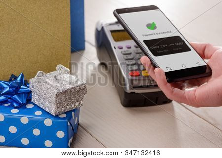 Man Buying Holiday Gifts And Paying With His Phone Successfuly