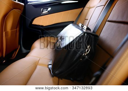Business Leather Briefcase On Backseat Of Luxury Car With Back Lit