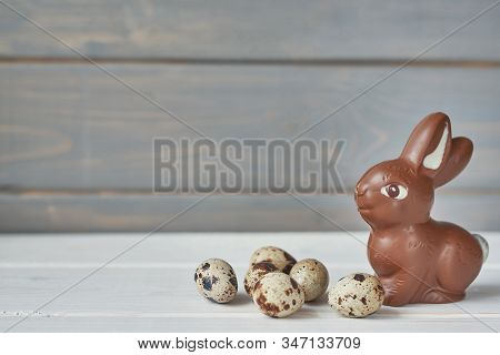 Delicious Chocolate Easter Bunny And Eggs On Wooden Background. Easter Greeting Card Template With C
