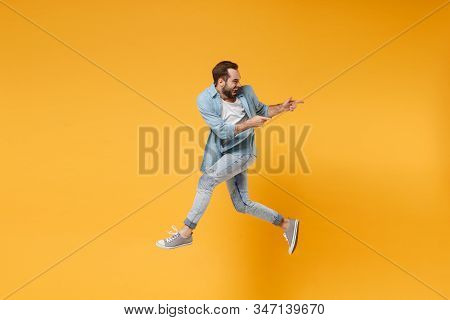 Funny Young Bearded Man In Casual Blue Shirt Posing Isolated On Yellow Orange Background, Studio Por