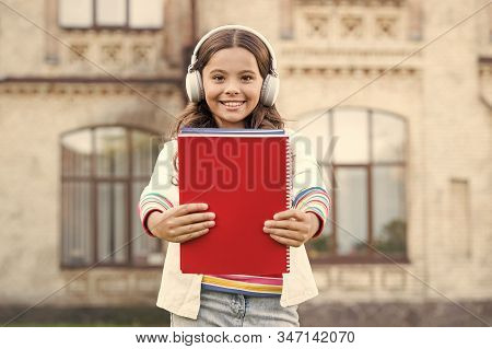 An Awesome Way Of Learning A Language. Little Girl Learning English Language With Audio Book. Happy