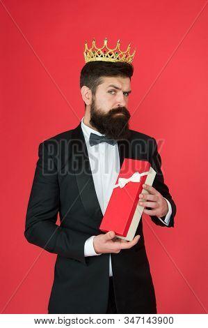 Being Complete Egoist. Egoist Hold Present Box Red Background. Bearded Man Wear Crown. Egoist Or Big