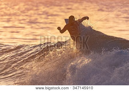 Surfer Contestant In Contest Jersey Is Silhouetted Against The Reflective Ocean Water During Golden