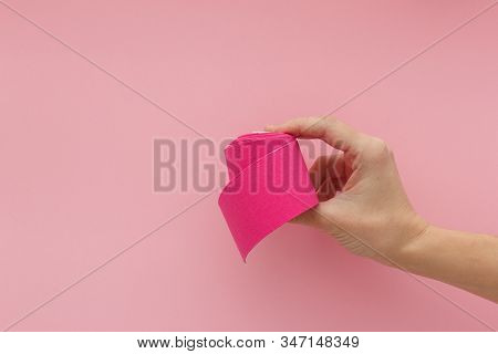 Tired Hand With Violet Kinesiology Tape Isolated On Pink Background. Physiotherapy Tape For Wrist Pa