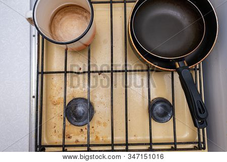 Dirty Unhygienic Surface Of Kitchen Gas Stove With Grease And Soot Stains With Kitchenware Pans On I