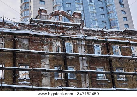 Background - Wall Of An Old Dilapidated Building In Scaffolding Against The Background Of A Modern M