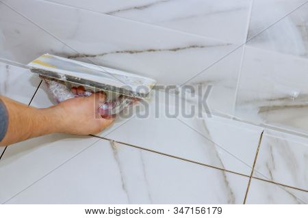 Bathroom Tiling By Manual Worker Grouting Tiles With Trowel Cement Mortar