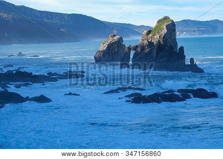 Cliffs, Reefs In The Coastal Waters Of The Ocean. Coastal Stones Lit By The Rays Of The Setting Sun.
