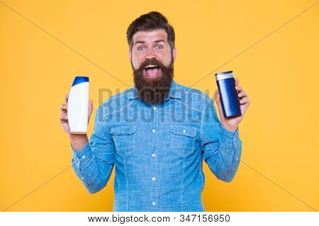 Grooming At Every Opportunity. Bearded Man Hold Shampoo Bottles Yellow Background. Cosmetics And Toi