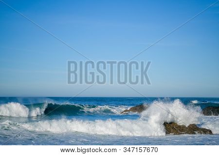 Large Ocean Waves Crash Against Coastal Stones On A Clear Sunny Day On The European Coast. Winter Ho