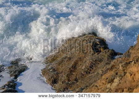 Large Ocean Waves Crash Against Coastal Stones And Rocks On A Clear Sunny Day On The European Coast.