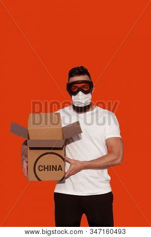 Man In Protective Goggles And Surgical Mask Unpacking Cardboard Box From China. Novel Coronavirus -