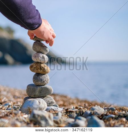 Close Up Of Young Man's Hand Lays A Stone On A Stone Cairn
