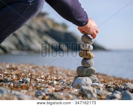 Young Man's Hand Lays A Stone On A Stone Cairn On The Beach