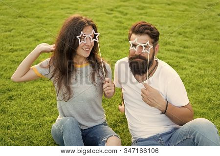 Photo Booth Party For Lovers. Romantic Couple Smiling With Happy Party Look On Green Grass. Happy Gi