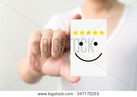 Customer Service Experience And Business Satisfaction Survey. Man Holding Card With Smiley Face With
