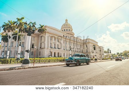 A Vintage American Retro Car Rides On An Asphalt Road In Front Of The Capitol In Old Havana. Tourist