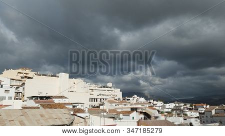 White Spanish Village With Dark Rain Clouds Looming